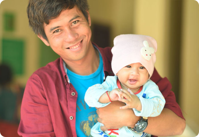 doctor holding a smiling baby