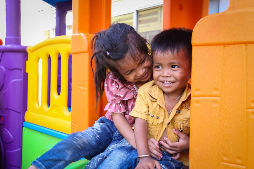 Two children sitting on a play structure