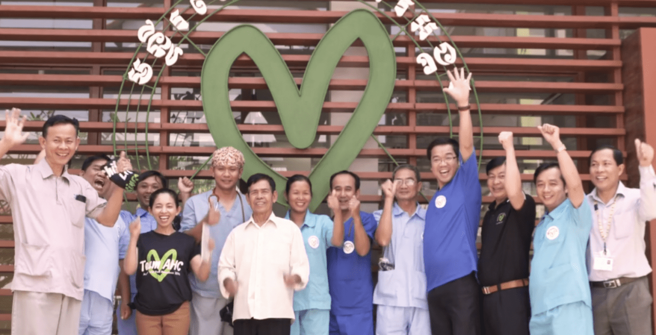 Group of people posing in front of a hospital sign